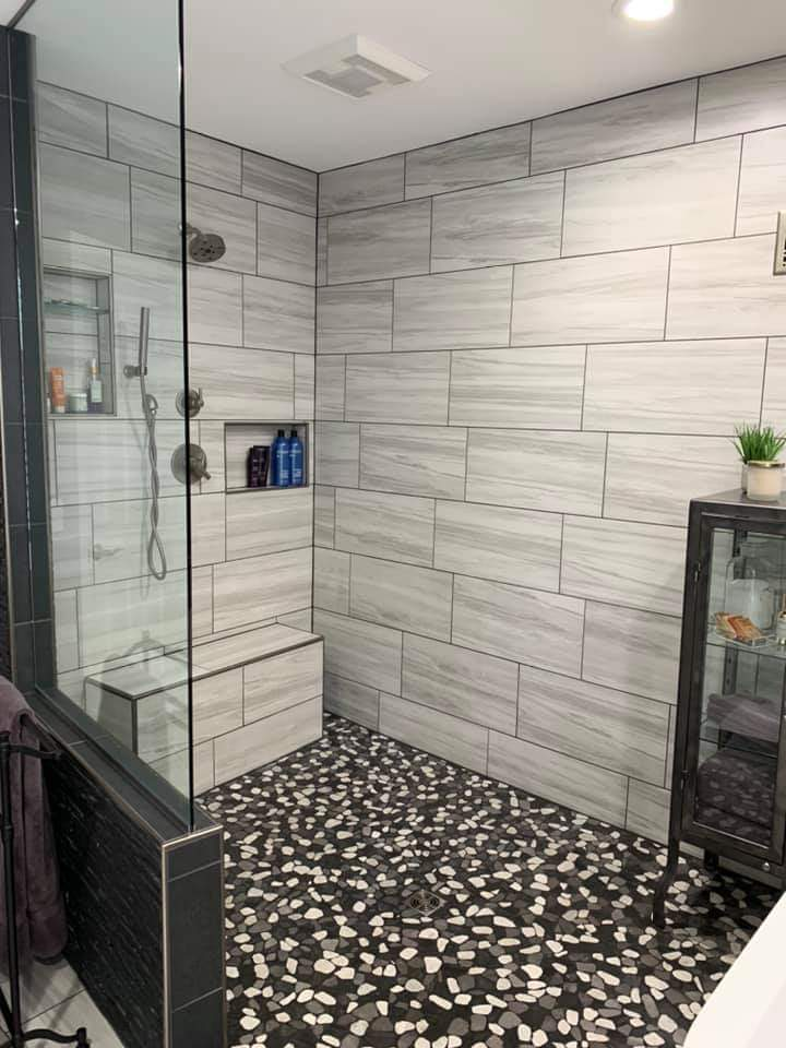 modern gray tile shower with a bench and a stone floor