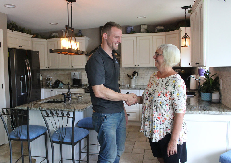 Kleeberger Contracting Services shaking hands with a satisfied customer in the customer's updated kitchen