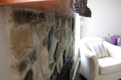 stone fireplace with a live edge wood mantle