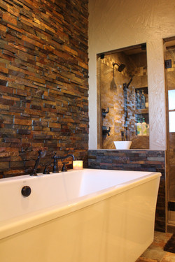 stand alone tub with a beautiful earth tone stone accent wall next to a tile shower