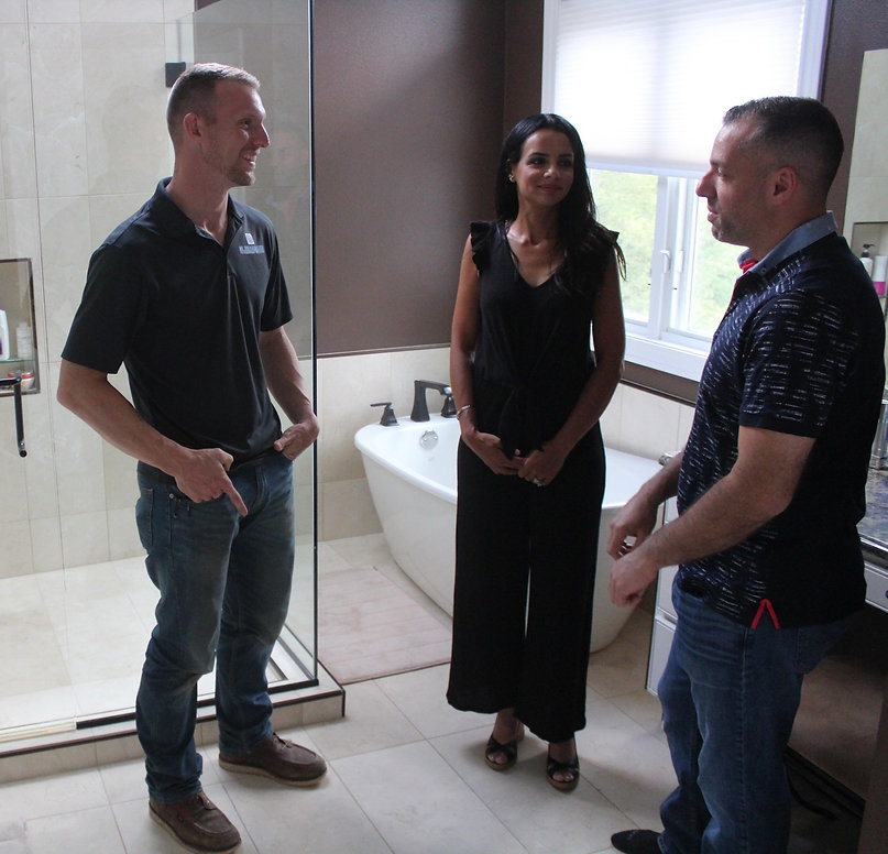 Kyle with homeowners standing in their remodeled bathroom completed by Kleeberger Contracting