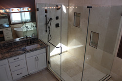 walk-in shower with glass doors along with a vanity with a granite countertop