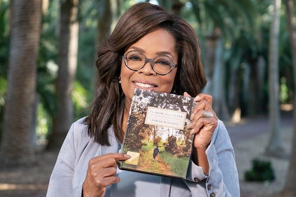 Oprah Winfrey holds a book to discuss during her Book Club