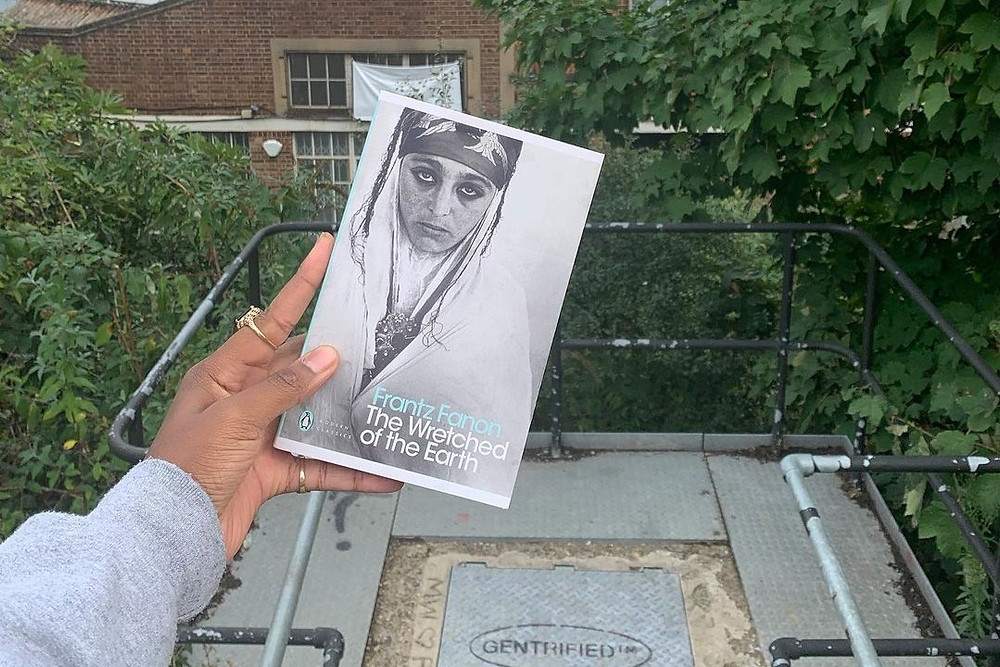 Book Club OKHA shares a photo of a hand holding a copy Frantz Fanon The Wretched Of The Earth