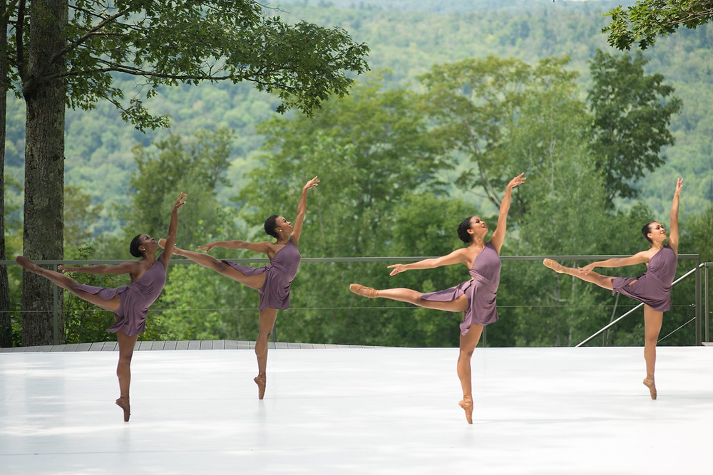 Four Black Ballet dancers in purple dresses dancing on stage for the collage dance collective