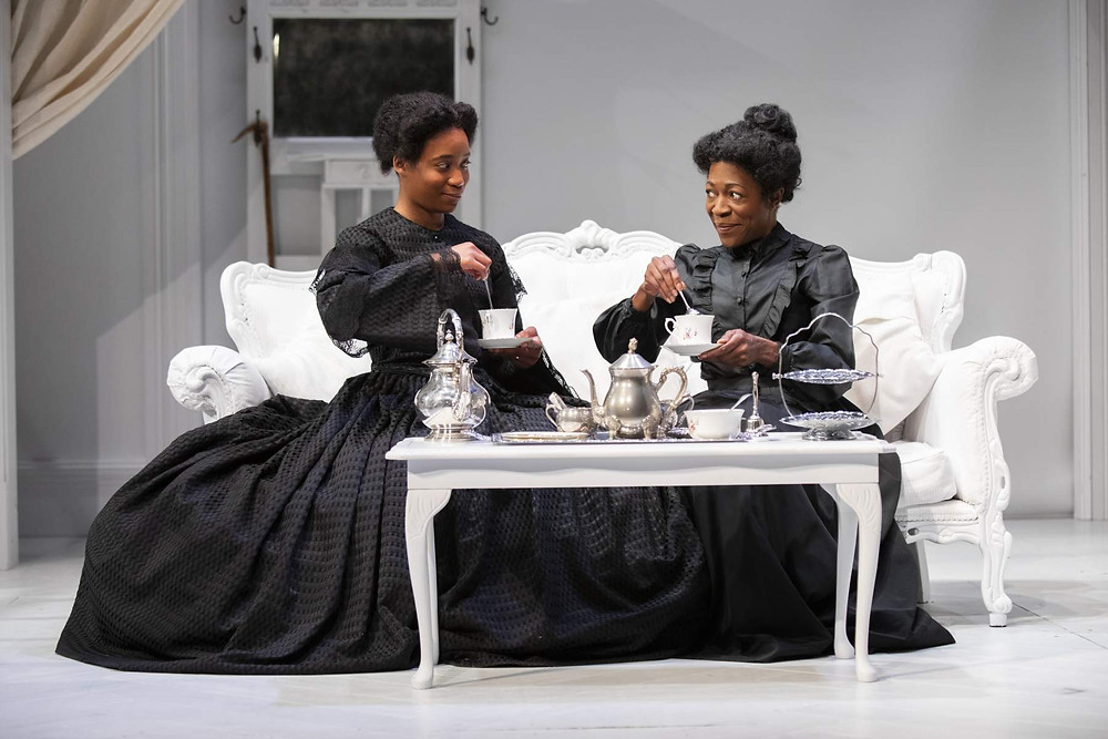 Two black female actresses perform on stage in black Edwardian dresses, stirring tea during a Eclipse theatre production