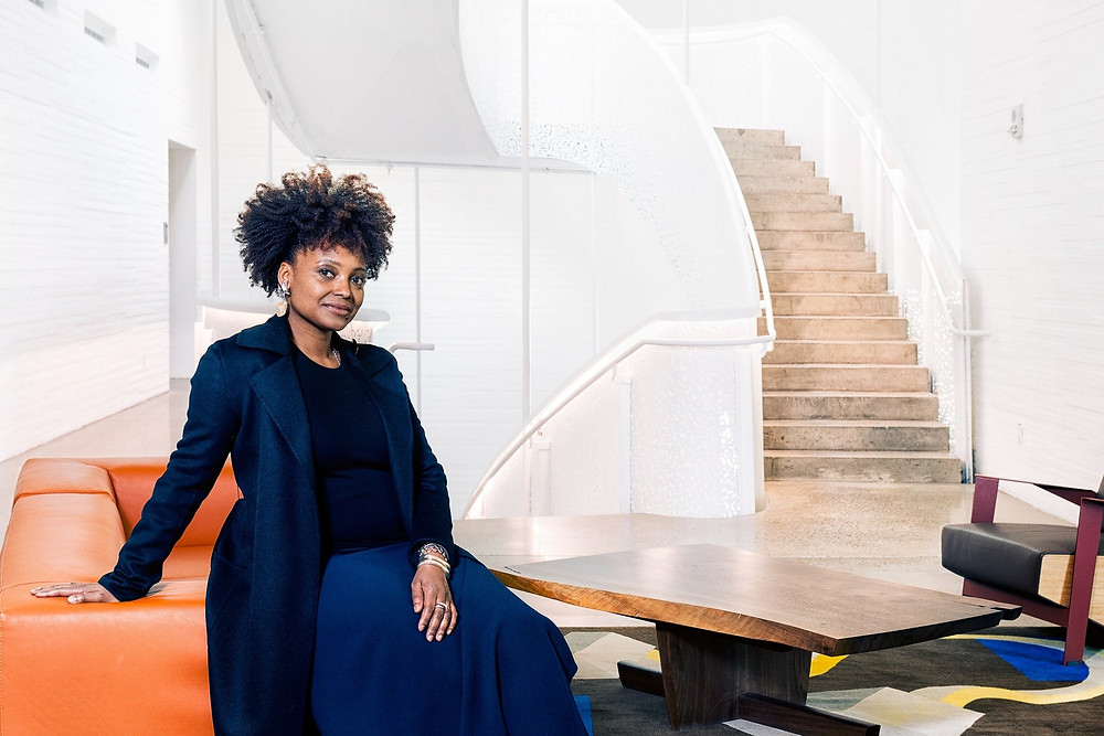African-American female poet Tracy K. Smith sits on an orange chair smiling at the camera in navy blue