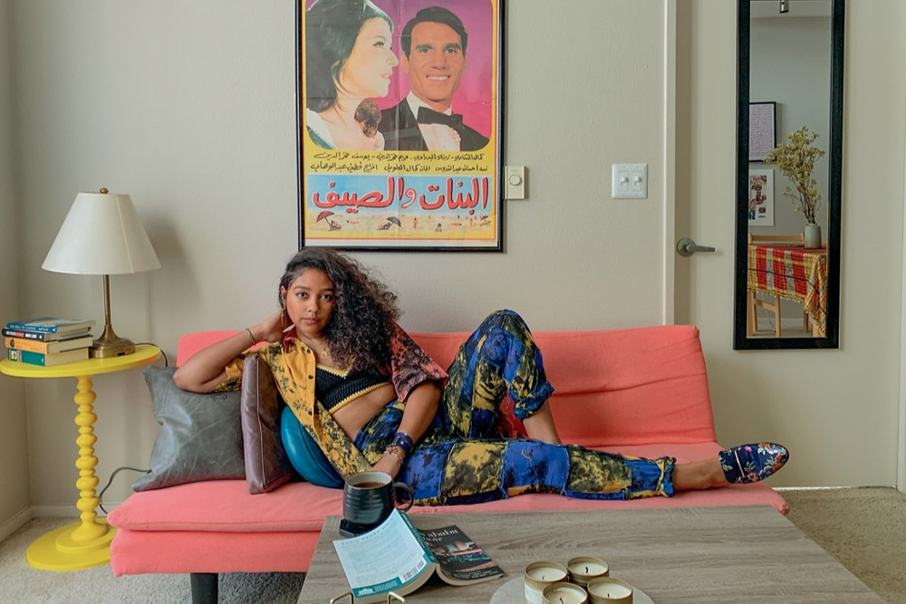 African-American female poet Safia Elhillo lays on a peach sofa in front of a vintage arabic movie poster.