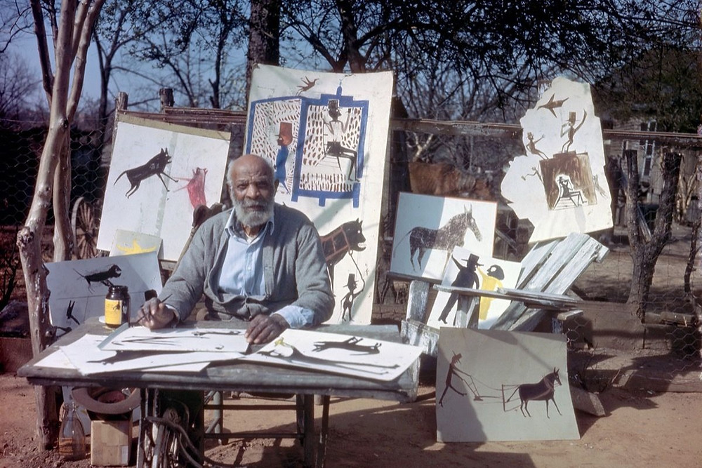 Black outsider artist Bill Traylor, proudly posing with many of his drawings of animals and people