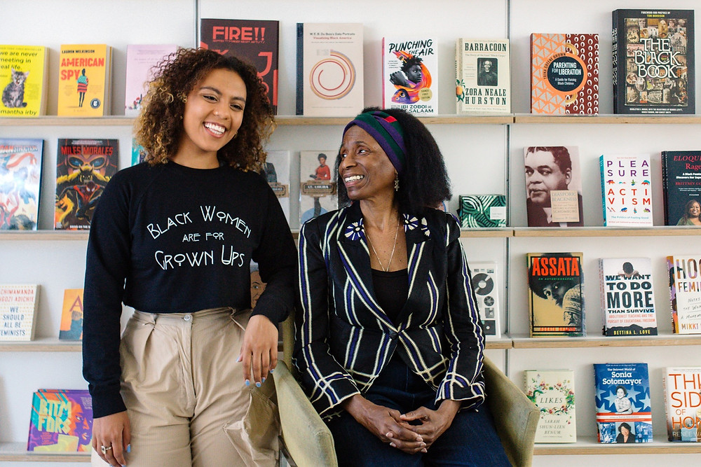 A photo of two smiling employees of the The Schomburg Shop and bookstore that stells  material surrounding and supporting black culture