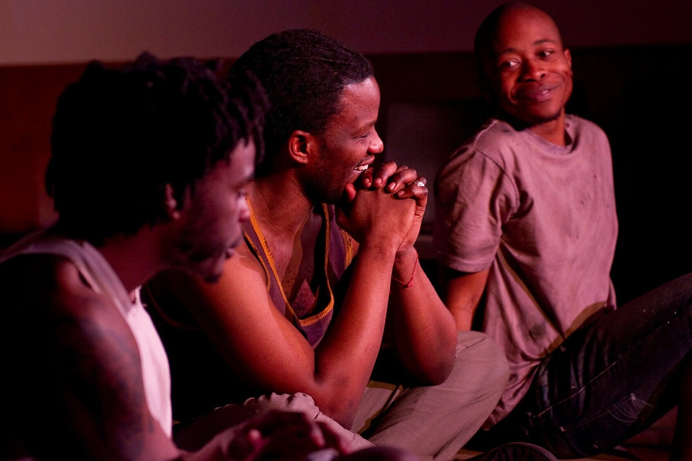 Black actors sit and smile as a part of the black british theatre company Tangle
