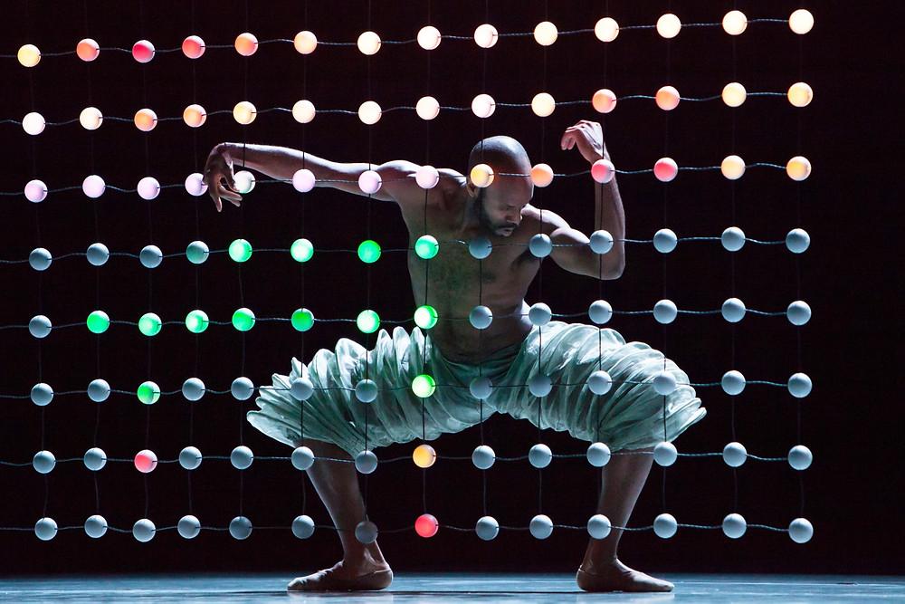 Black male ballet dancer poses behind multi coloured lightning representing Alonzo King LINES Ballet