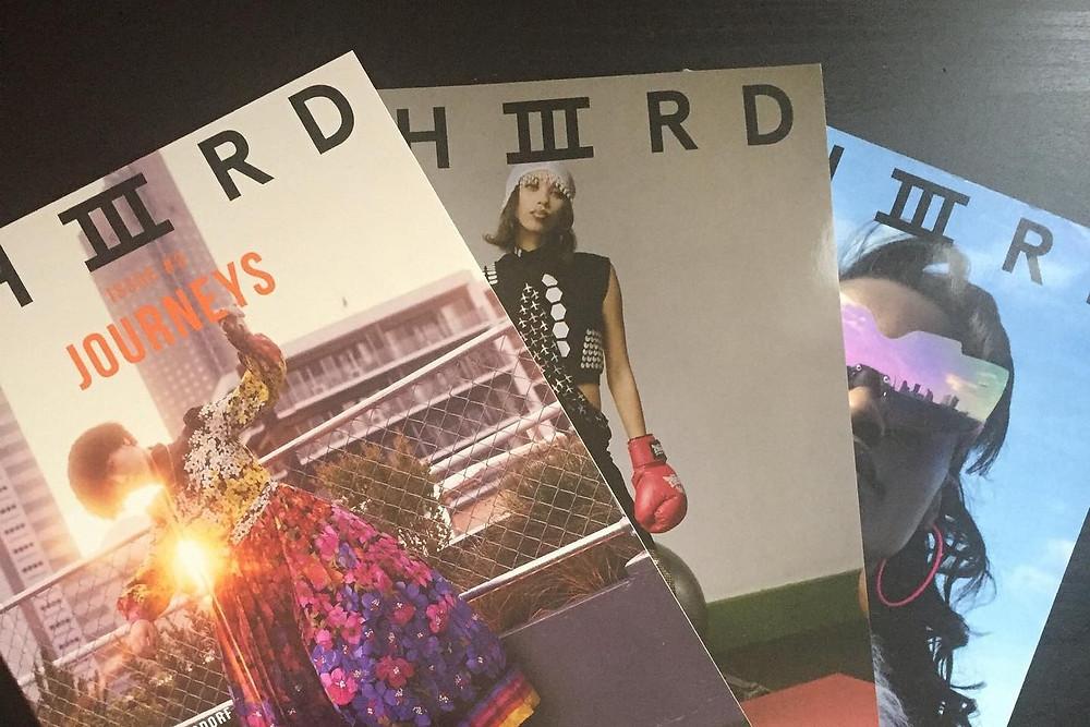 Three copies of Black owned British Magazine Thiiird on a black background