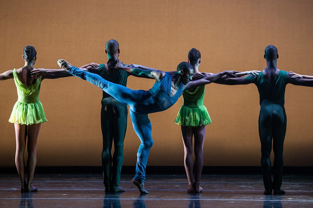 Five black male and female ballet dancers pose on stage in blue and green costumes representing Dance Theatre Of Harlem