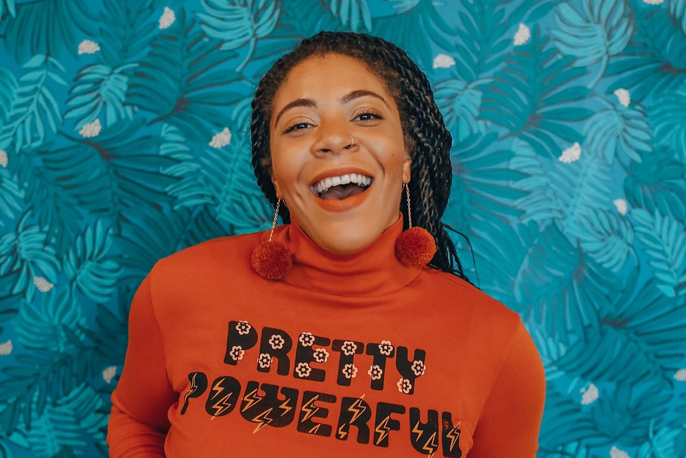 African-American female poet Arielle Estoria smiles in an orange sweater with matching earrings and in front of a turquoise floral background