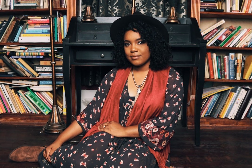 American-American female poet Morgan Harper Nichols sits with her legs crossed in front of a library