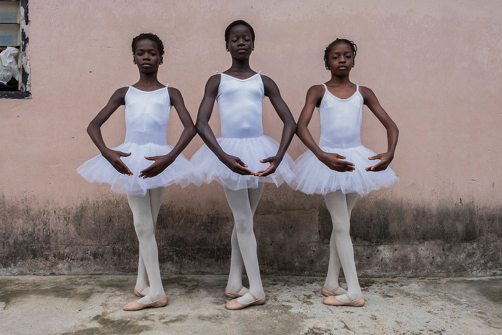 Three female ballet dancers pose in white tutus in front of a pale pink wall representing Leap Of Dance Academy