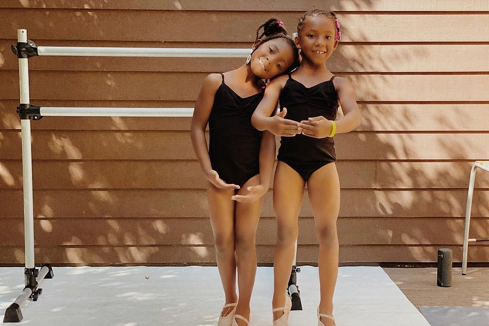 Two young black female ballet dancers pose in front of bar smiling promoting Ballet In Color