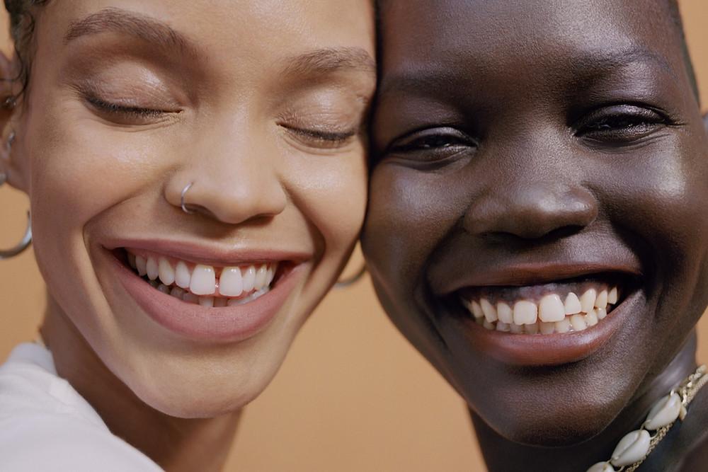 Two Black Female Models promoting Black owned vegan make up brand Uoma Beauty smiling