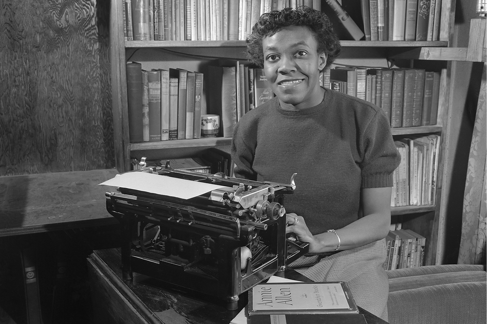 A black and white photograph of African-American female poet Gwendolyn Brooks with her typewriter in front of a library