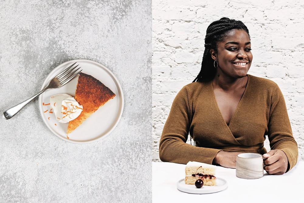 Black female baker Benjamina Ebuehi drinking tea promoting her cookbook The New Way To Cake with a orange and cream cake