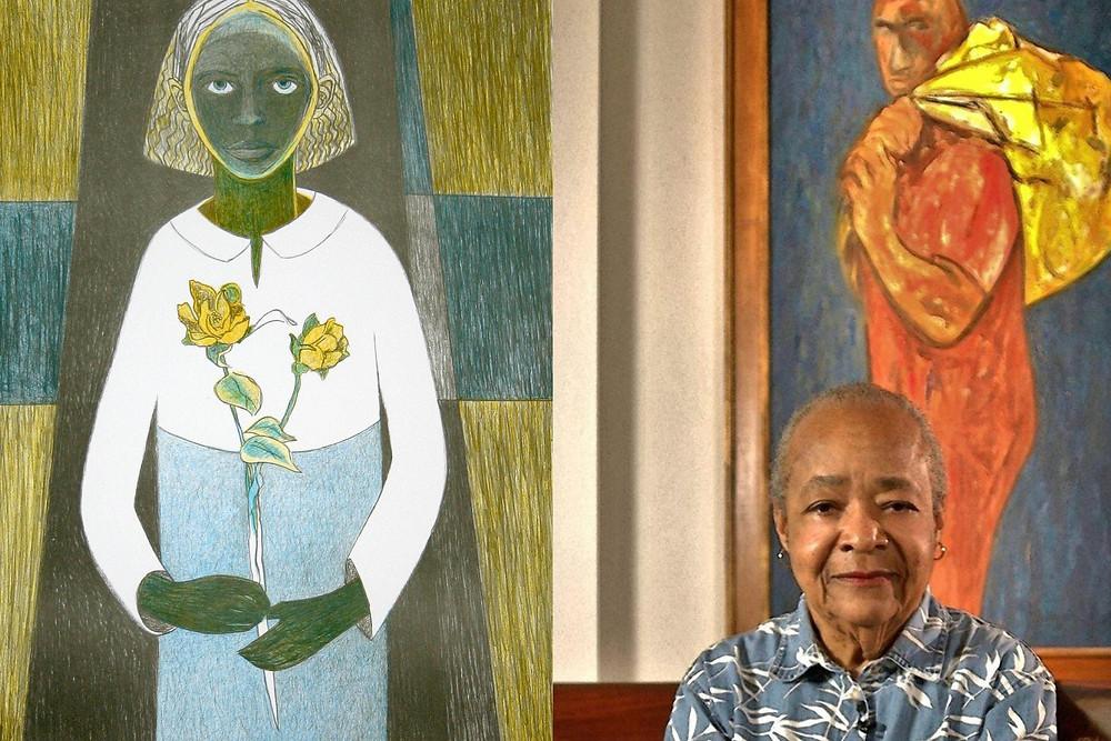 Samella Lewis sitting next to artwork of woman holding yellow flowers