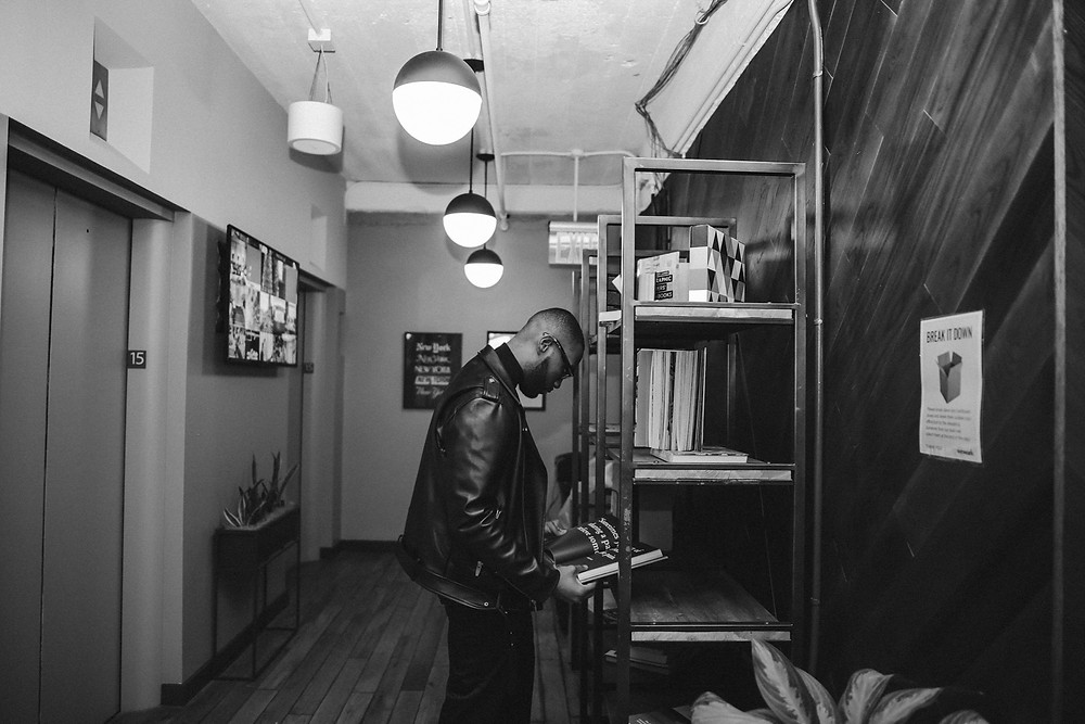 Black and white photo of a black man reading from Black Men Book Club