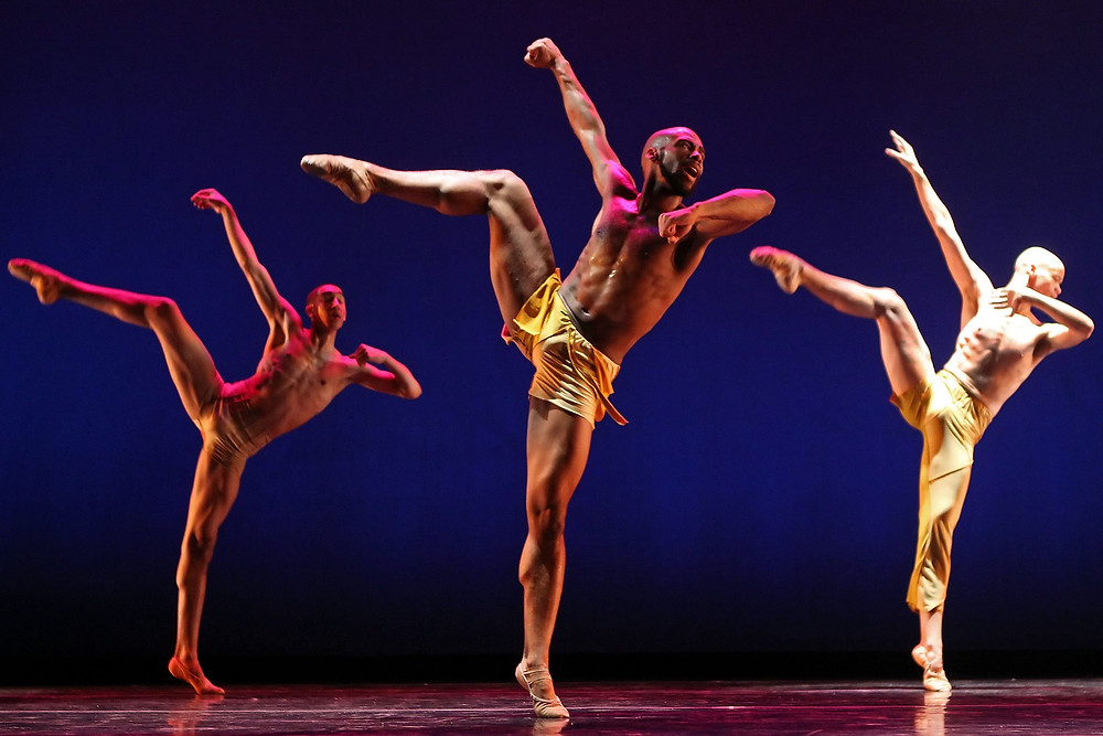 Three Black Male Ballet dancers in Gold shorts dancing on stage for Complexions Contemporary Ballet