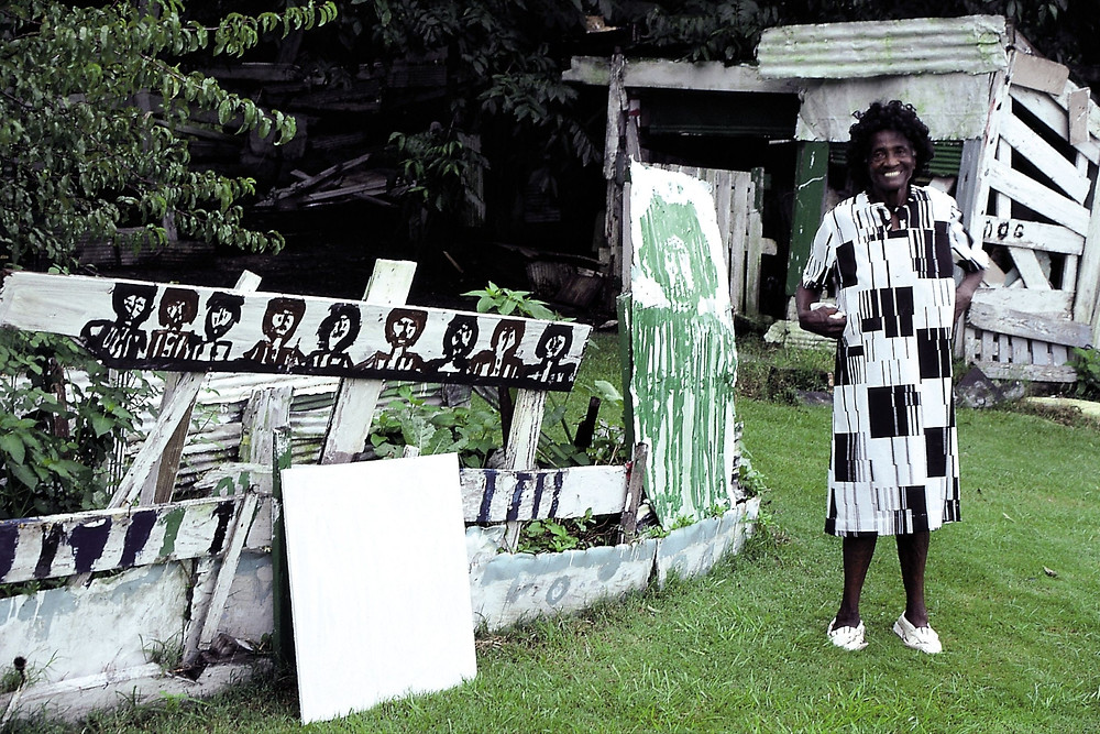 Black outsider artist Mary T. Smith stands in her yard proudly in front of her paintings