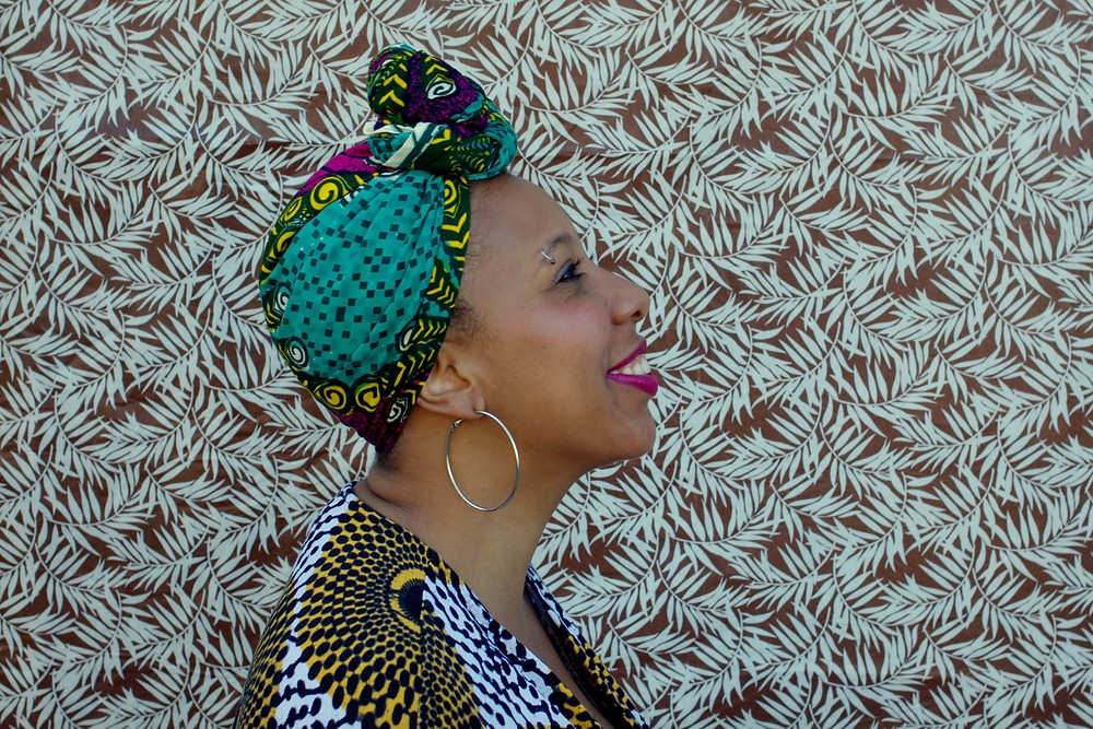 African-American female poet Morgan Parker stands in smiling in a patterned headscarf and dress in front of leaf wallpaper