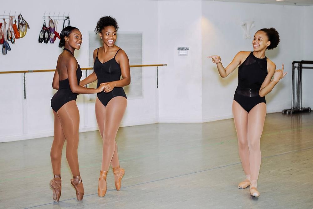 Three Black Female Ballet dancers in black leotards dancing posing to promote The Hiplet Ballerinas