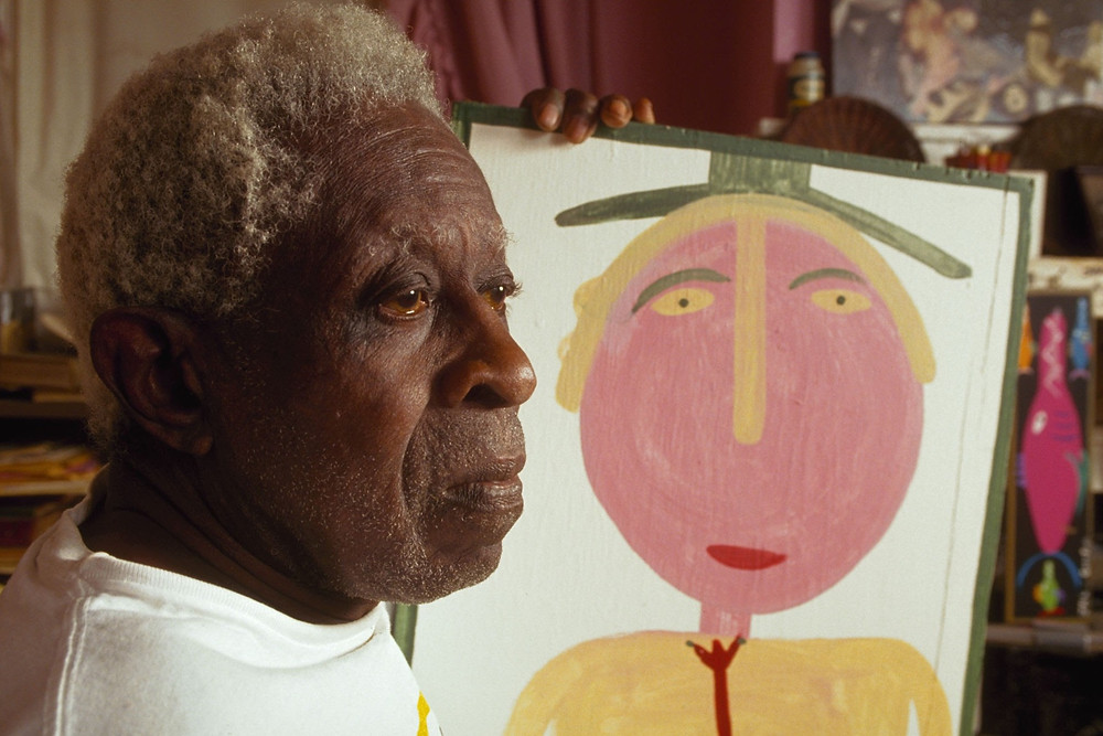 Black outsider artist Moses Ernest Tolliver poses with one of his artworks