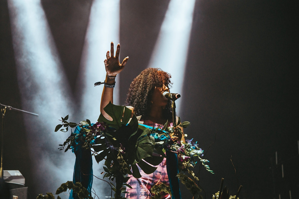 African-American female poet Aja Monet speaks poetry on stage with her arm raised