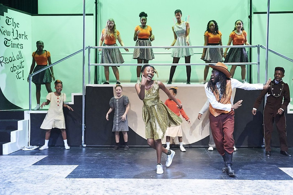 Black children perform on stage, dancing and singing for Theatre Peckham