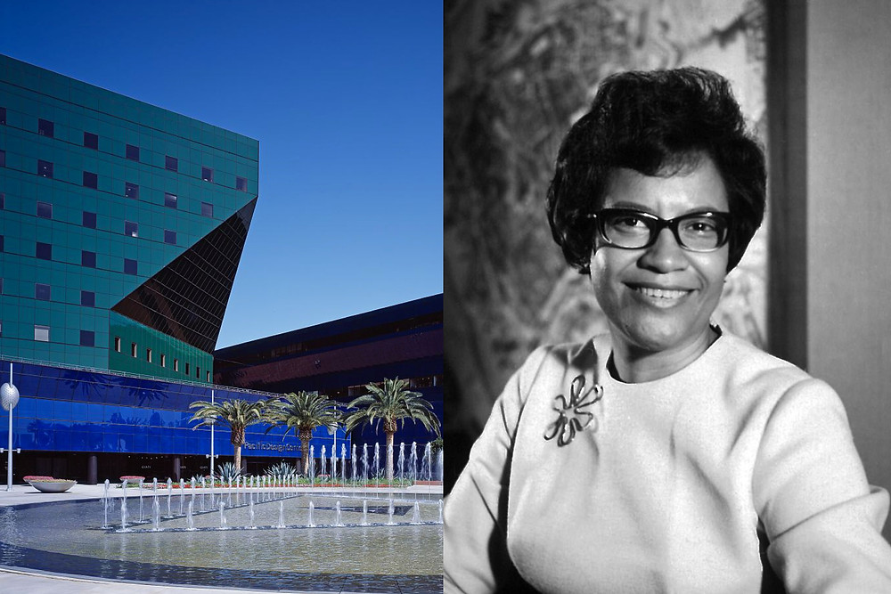 Black female architect Norma Sklarek smiles proudly alongside a blue and green modern building she designed.