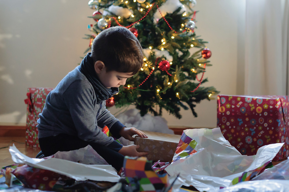 child unwrapping christmas gifts