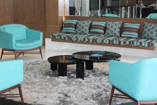 Sala de estar com tapeçaria de bancada e poltronas com tecidos coordenados, tapete com medida especial para o local