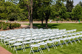White chairs set up for an outdoor weddi