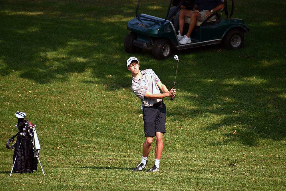 Senior Ethan Pogemiller eyes the green during his approach.