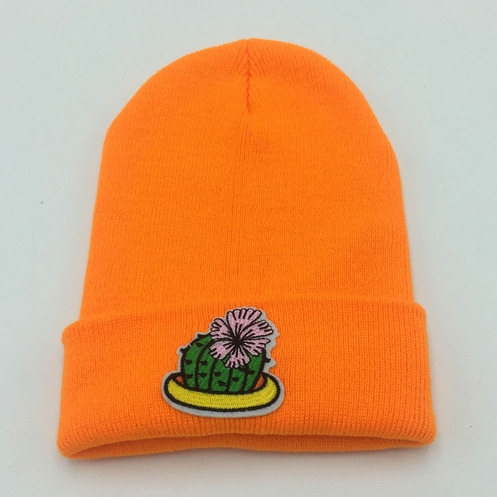 726bbc8c Designed and assembled by hand in the UK. A soft, orange beanie with  embroidered cactus design.
