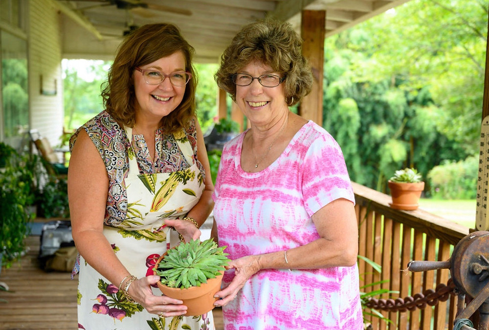 Two women holding a plant together