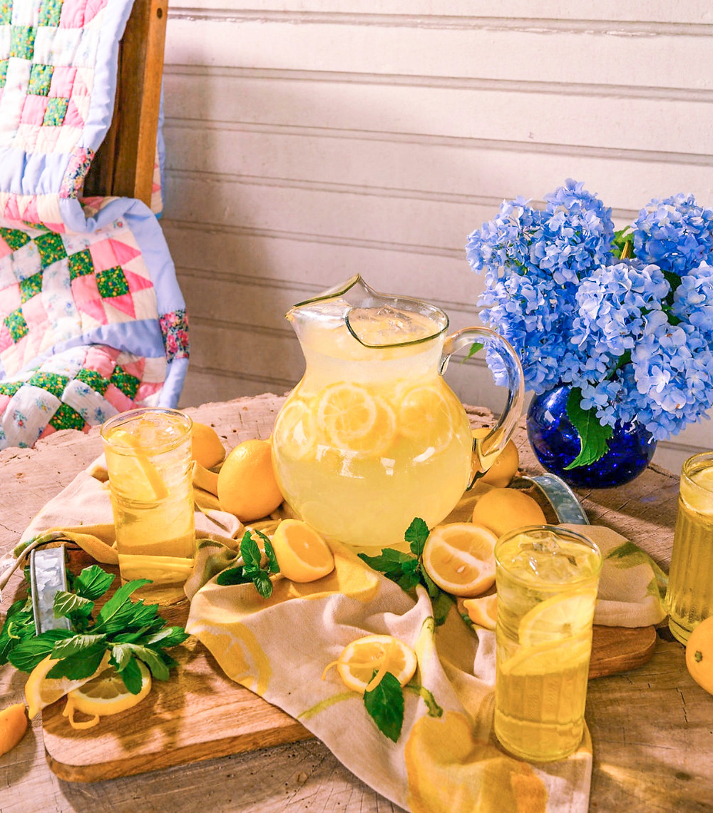 A table with a bouquet of blue hydrangea and a pitcher and two glasses of lemonade