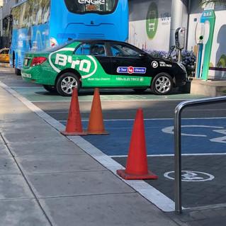 Taxi eléctrico al lado de un bus eléctrico