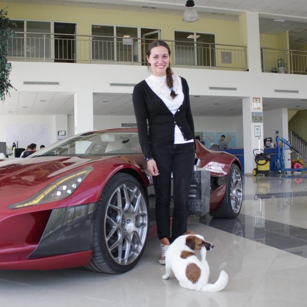 Monika con uno de nuestros autos de Gama Alta Eléctricos.
