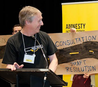 Ian, a white man with short grey hair in a black tee shirt, is standing at a podium while smiling at activists holding a banner about consultation behind him.