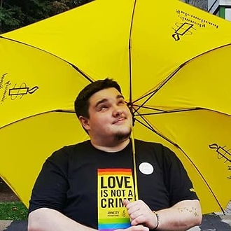 """Alex is a 30-ish white man with short dark hair, shown from mid-torso up. He is looking up and off to the side, and his hands are clasped in front of him holding a bright yellow umbrella over his head. He is wearing a black t-shirt with a rainbow graphic and the words """"Love is not a crime"""" on it over the Amnesty International logo."""