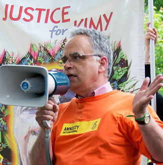 photo of Gord Barnes. Gord is a white man wearing an orange Amnesty shirt and glasses and short grey hair. Gord is shown at a public event making an emphatic hand gesture and speaking into a megaphone