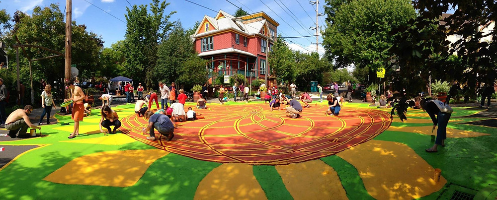 The first City Repair undertaking was colorfully painting the pavement of a neglected intersection of SE 9th Ave and SE Sherrett Street by members of its neighborhood.