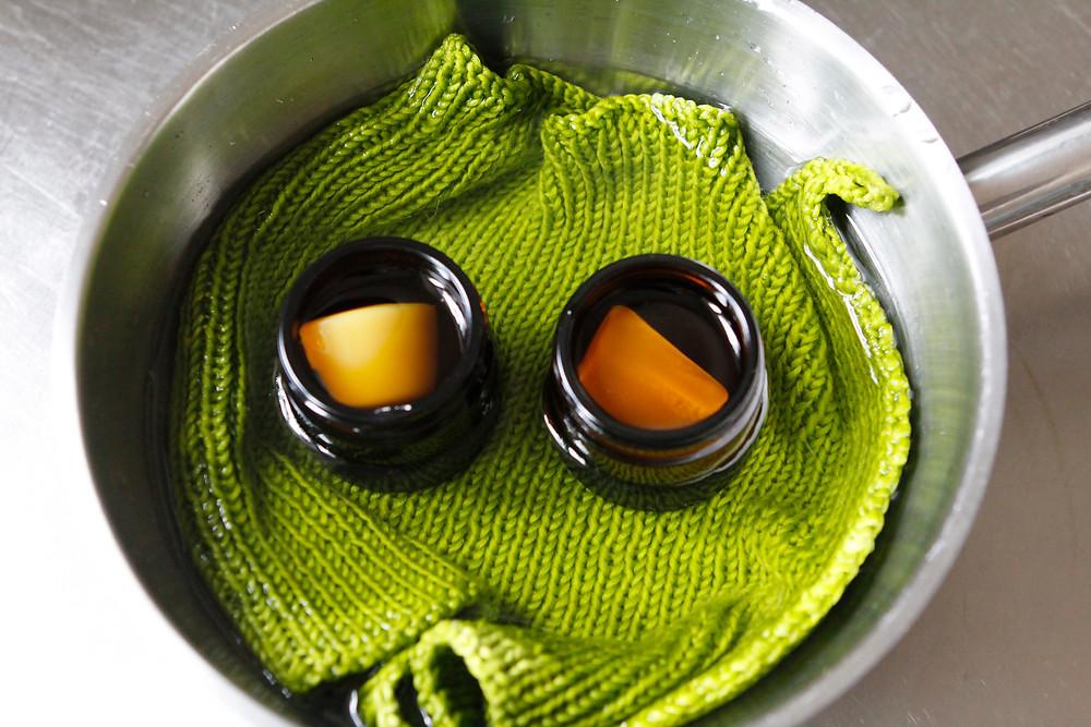 Bivax och olja i burkar i ett vattenbad.
