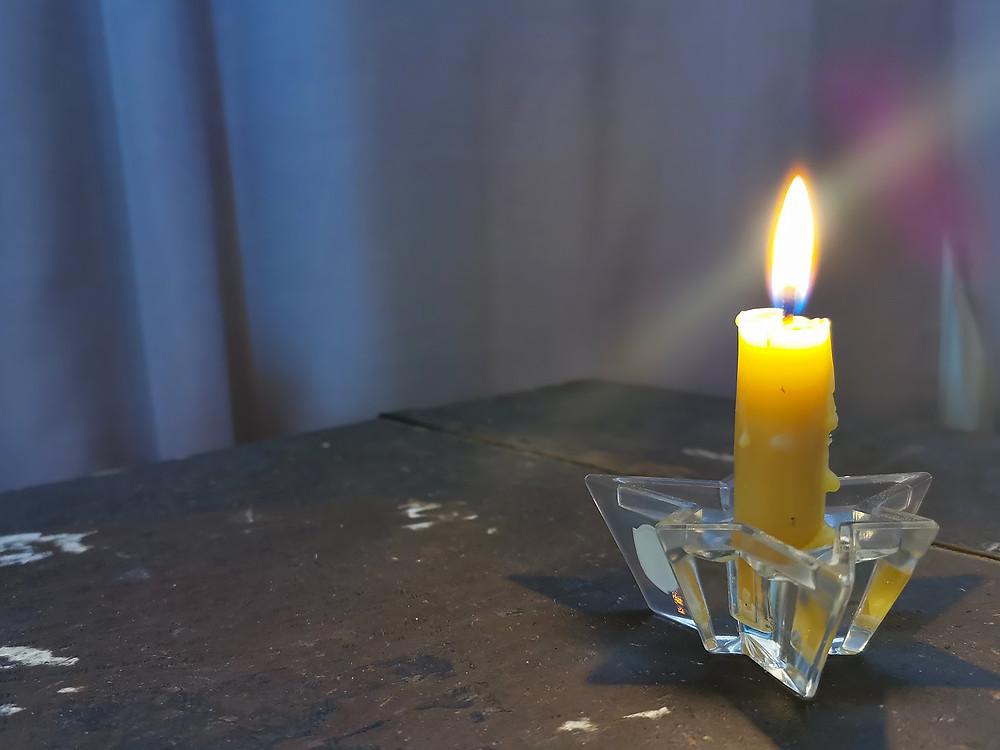 Ett gult bivaxljus som brinner på en mörkbrun kista.